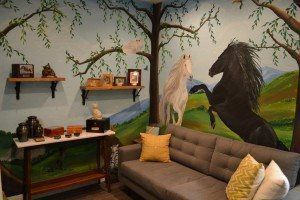 room with shelves on the wall, a gray couch, and a painted horse mural