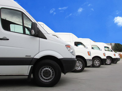 row of white vans in a parking lot
