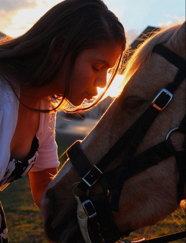 woman kissing horse's nose